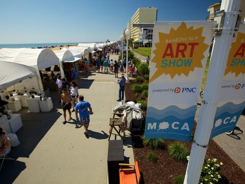 Passeio pelo Boardwalk Art Show em um dia de céu azul