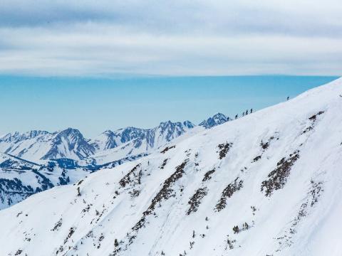 Esqui montanha acima durante uma corrida de esqui de longa distância do Shedhorn Skimo em Big Sky, Montana