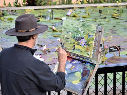 Artista pintando nenúfares no Civic League Park durante a competição nacional En Plein Air TEXAS e o Cinch Roping Fiesta no Texas